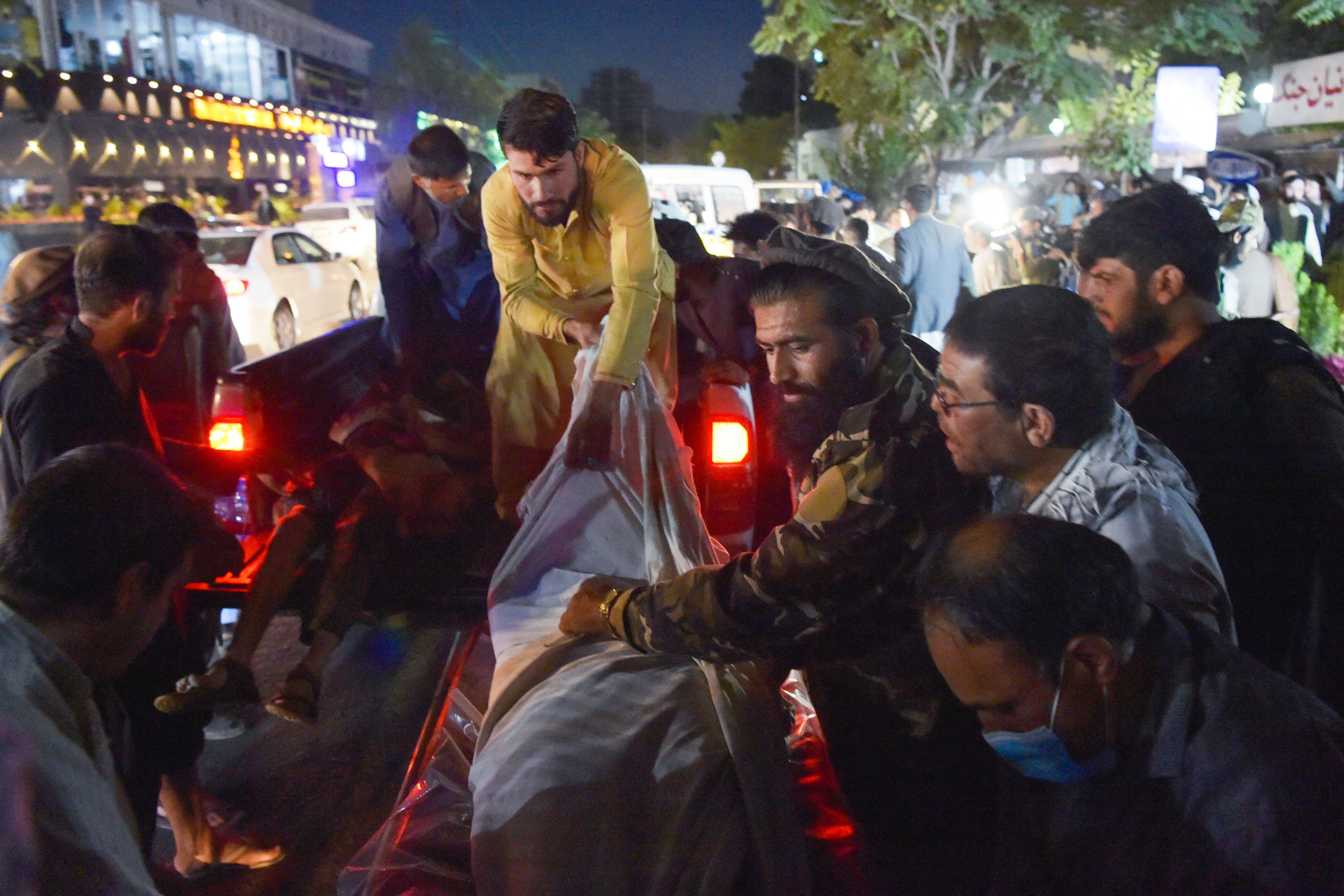 Volunteers and medical staff unload bodies at a hospital after a bomb blast in Kabul, Afghanistan, on August 26, 2021.