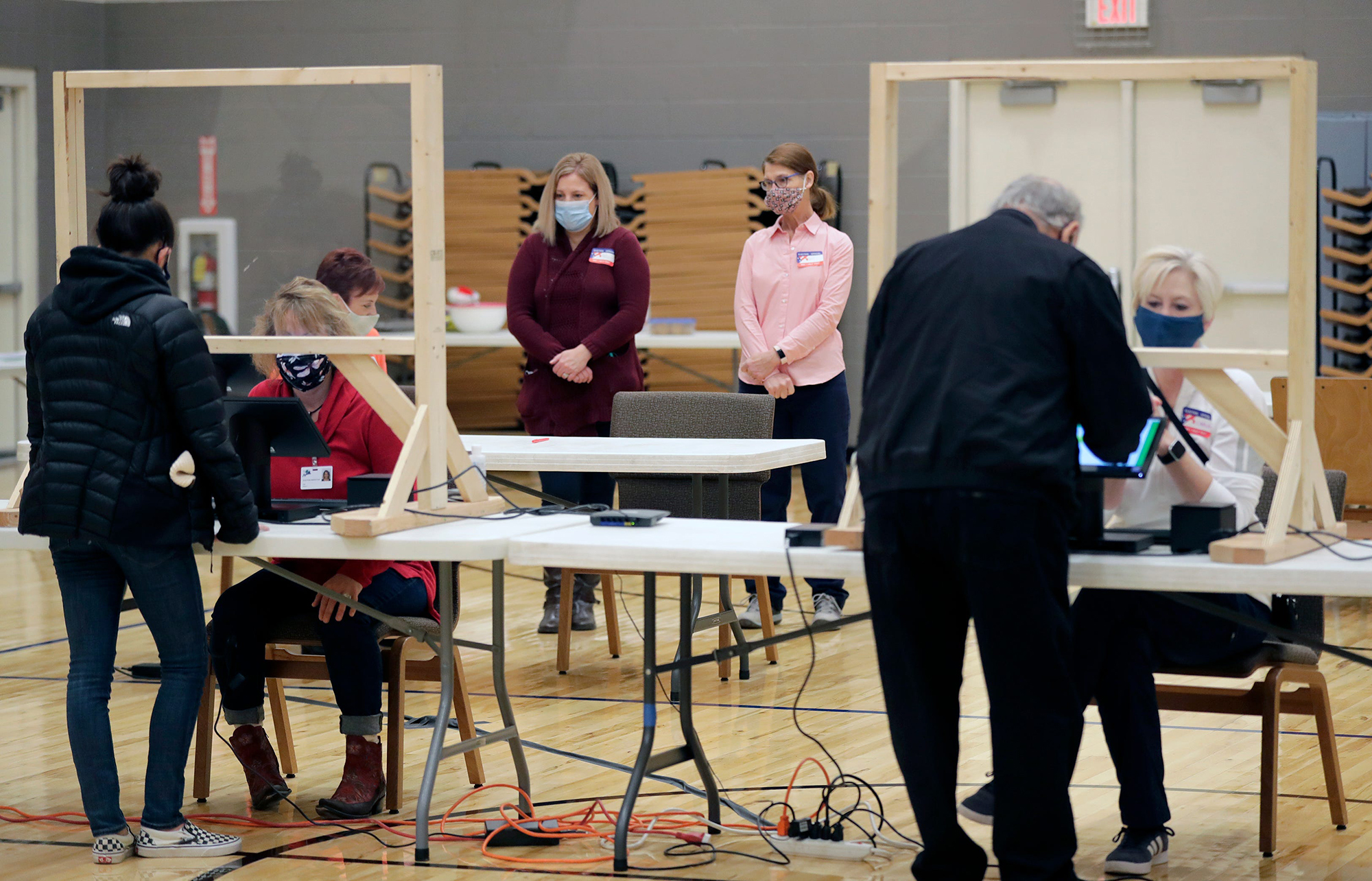 Poll observers watch as citizens receive their ballots to vote at Faith Lutheran Church Celebration Ministry Center on November 3, 2020, in Appleton, Wis.