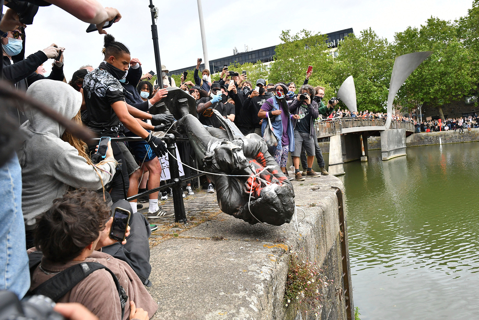 Protesters throw a statue of slave trader Edward Colston into Bristol harbor, during a Black Lives Matter protest rally, in Bristol, England, on June 7.