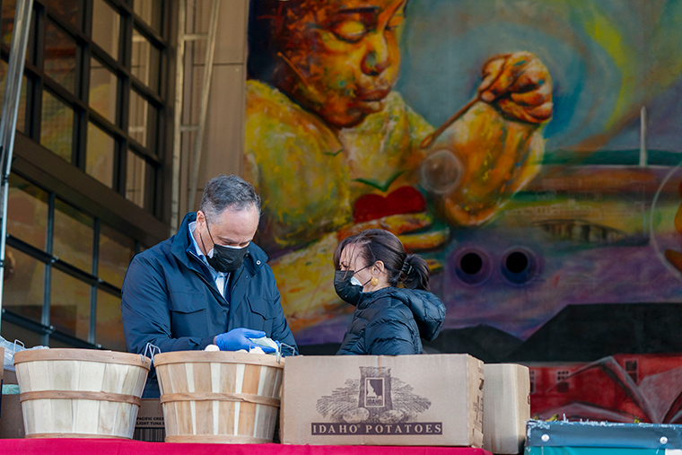 Vice President-elect Kamala Harris, right, and her husband Douglas Emhoff, pack grocery bags for those in need of food while volunteering during the National Day of Service, Monday, January 18, at Martha's Table in the southeast neighborhood of Washington, DC.
