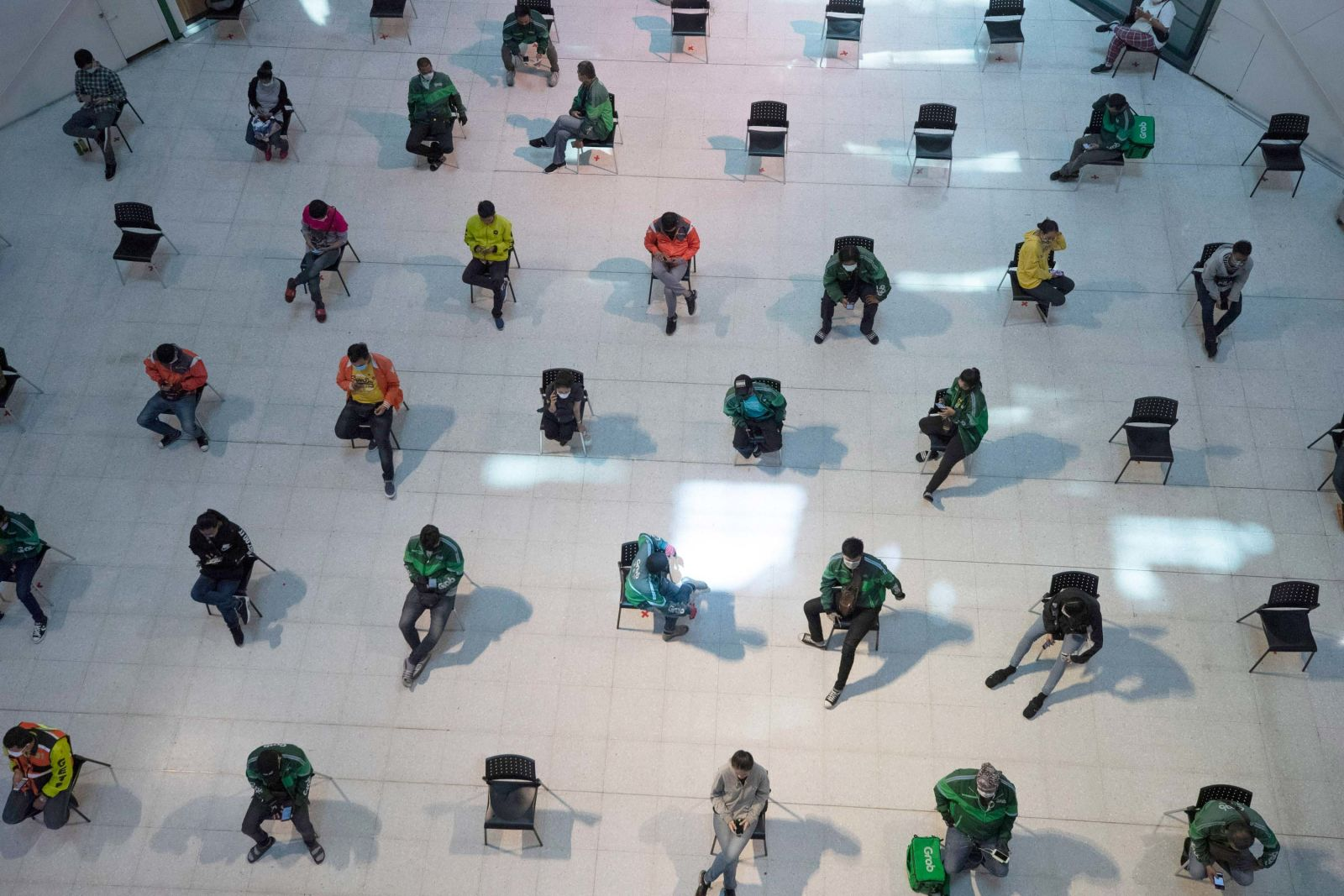 People practice social distancing as they wait for takeout food at a shopping mall in Bangkok, Thailand, on Tuesday.
