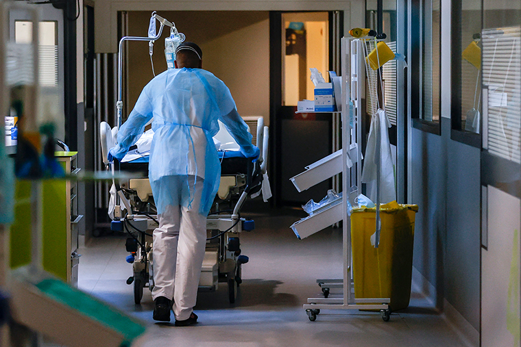 A patient infected with the Covid-19 is carryed by a stretcher bearer in an intensive care unit of the Hopital Delafontaine in the Saint-Denis surburb of Paris, on March 29.