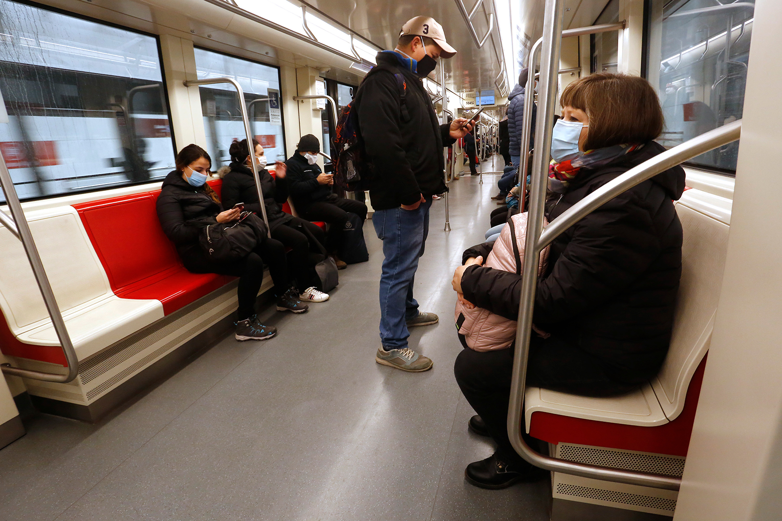 People wearing face masks ride the subway on June 16, in Santiago, Chile.