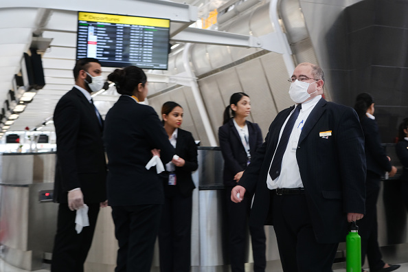 Airport employees wear medical masks at John F. Kennedy Airport in New York on January 31, 2020.