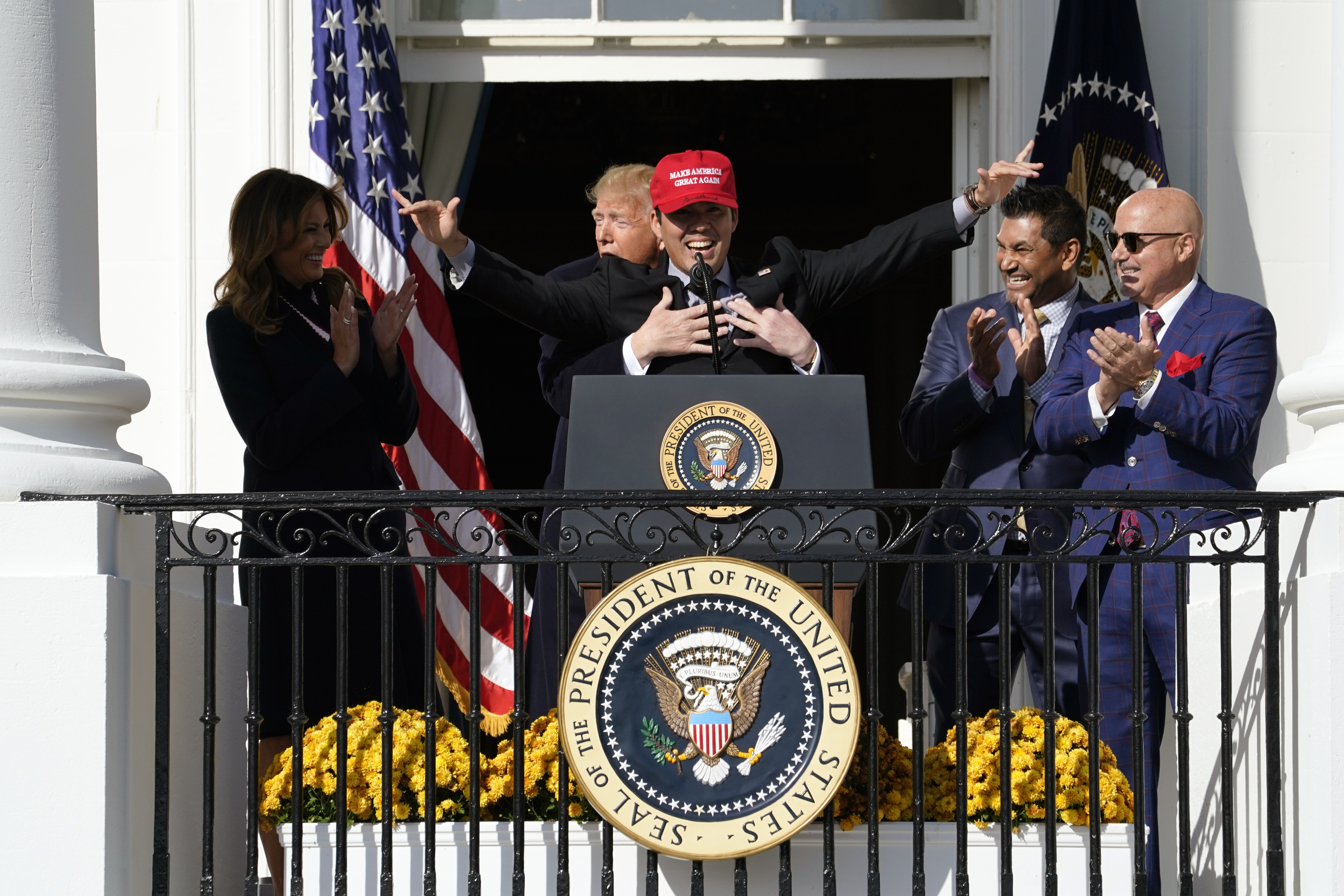 """Catcher Kurt Suzuki wears a """"Make America Great Again"""" hat as he is hugged by President Trump as he welcomes the 2019 World Series Champions, the Washington Nationals, to the White House"""