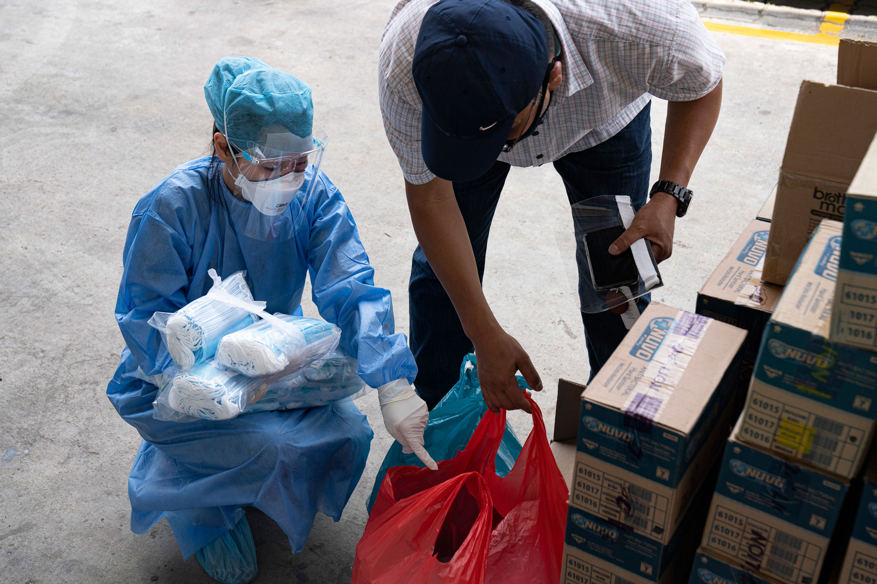 Volunteers for an NGO check out medical supplies to be distributed to migrant workers in a dormitory on April 17, in Singapore.
