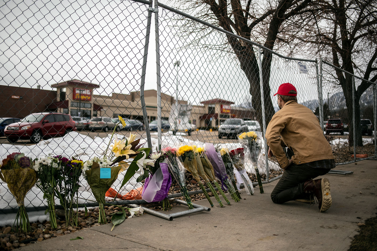 A mourner leaves flowers at a makeshift memorial outside of King Soopers grocery store in Boulder, Colorado, on March 23.