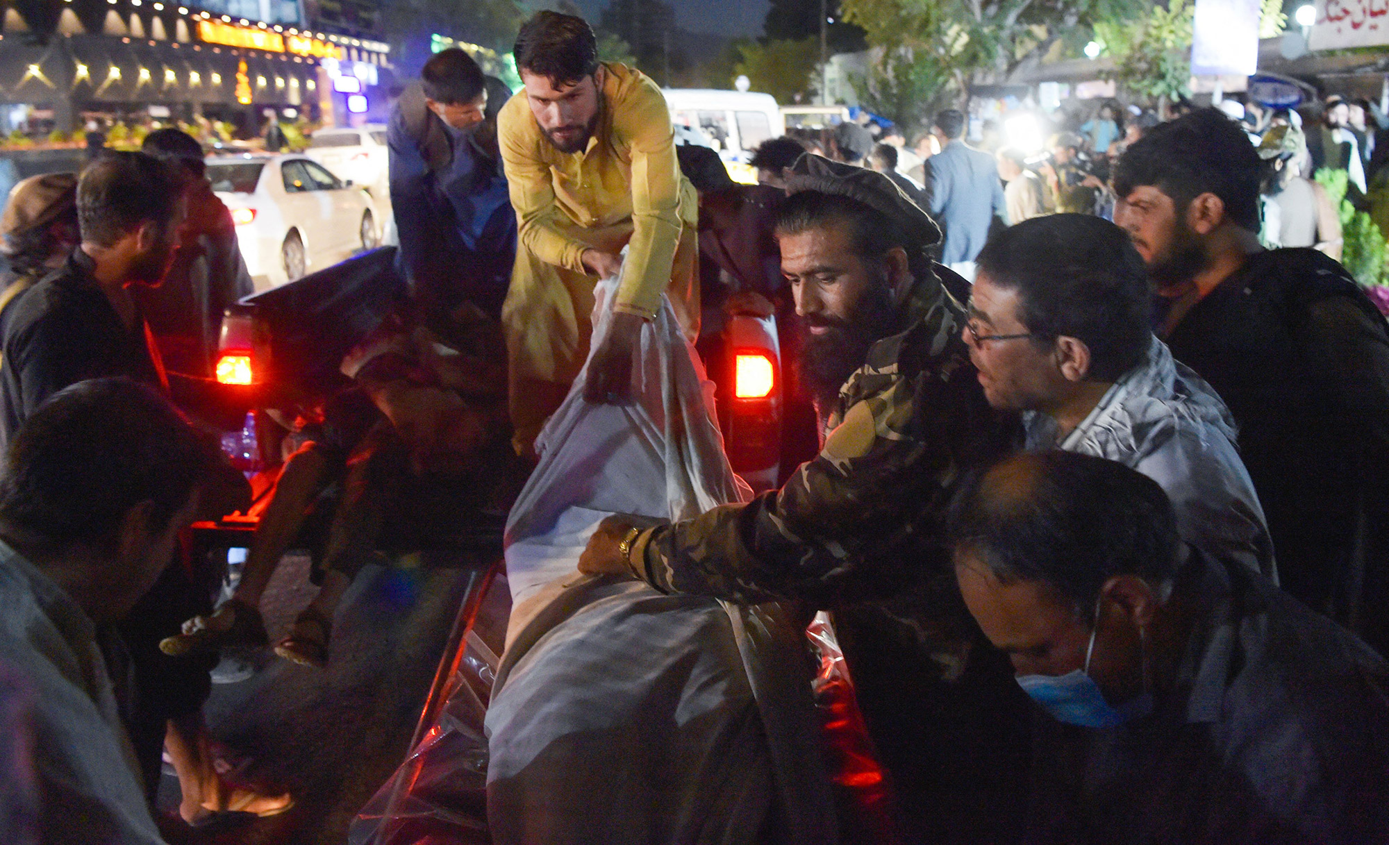 Volunteers and medical staff unload bodies outside a hospital after the bomb blasts at the Kabul airport on August 26.
