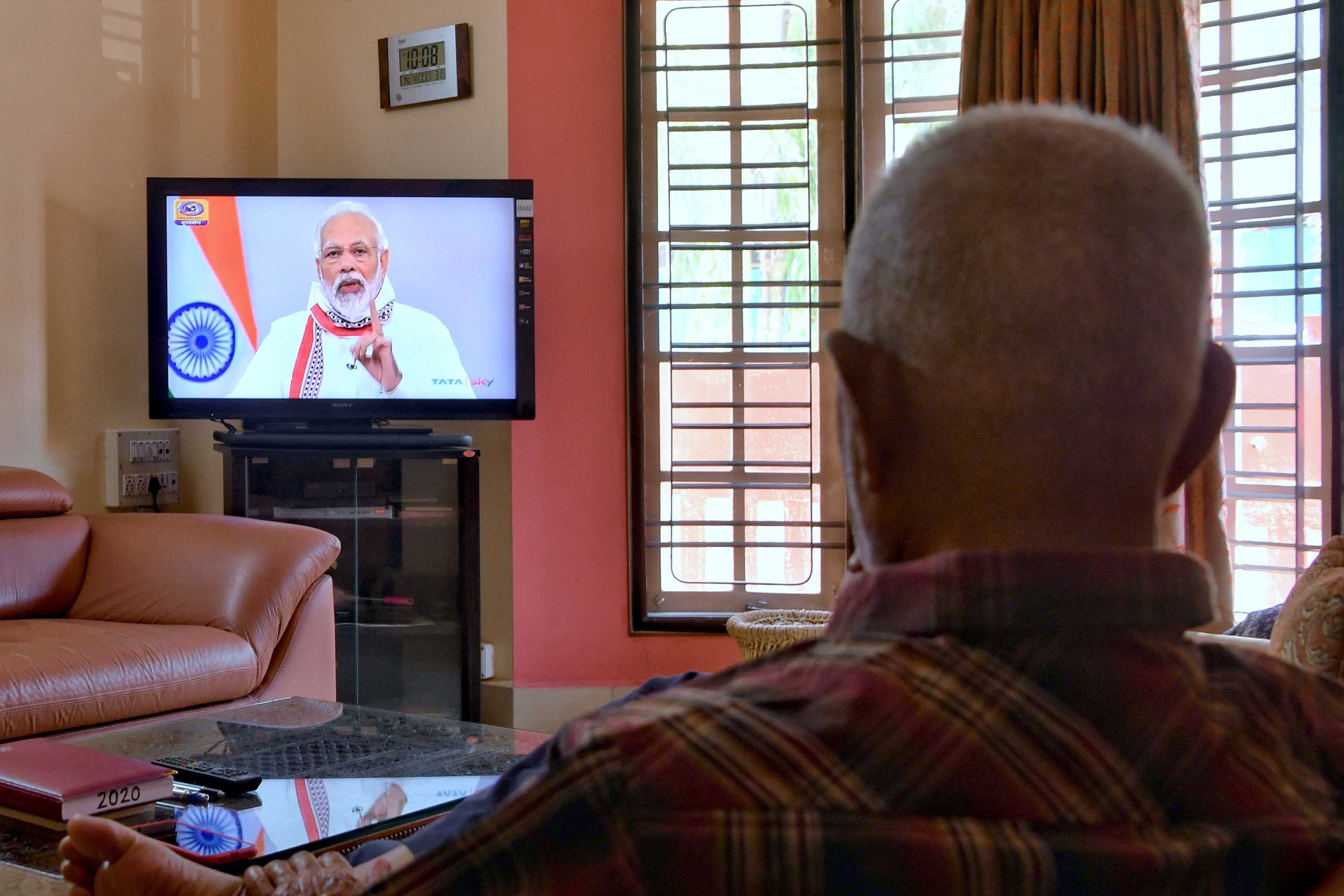 A man watches Indian Prime Minister Narendra Modi address the nation during a television broadcast in Bangalore, India, on April 14.