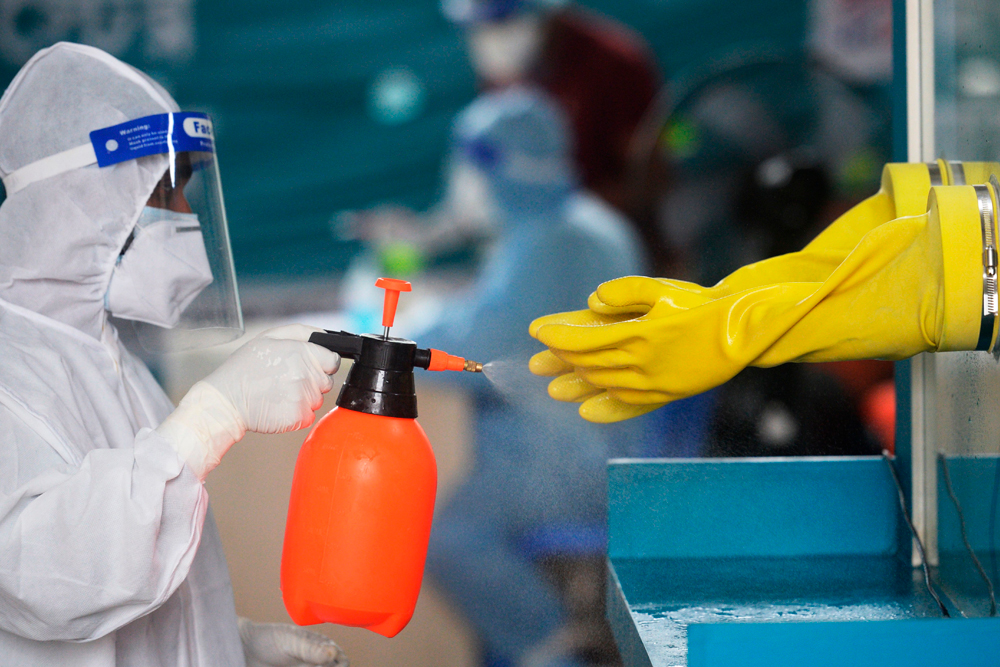 An employee of the Mugda Medical College and Hospital sprays disinfectant on gloves after a nasal swab Covid-19 test was administered in Dhaka on June 17.