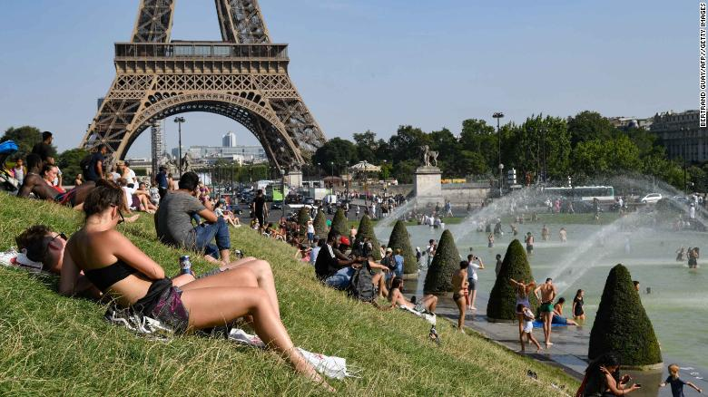 People sunbathe and cool off in the Trocadero Fountains in Paris on Tuesday.