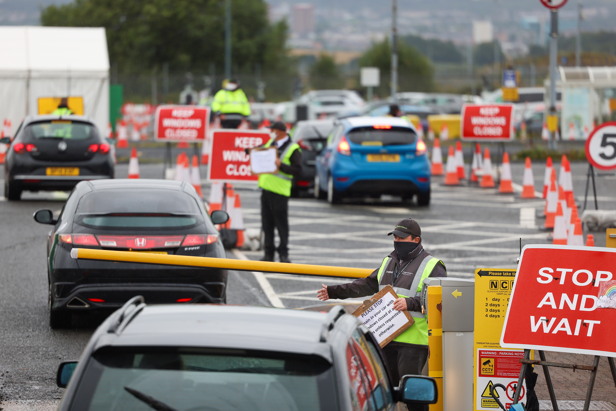 An employee directs members of the public to drive into a coronavirus testing center at Glasgow Airport on August 26 in Glasgow, Scotland.