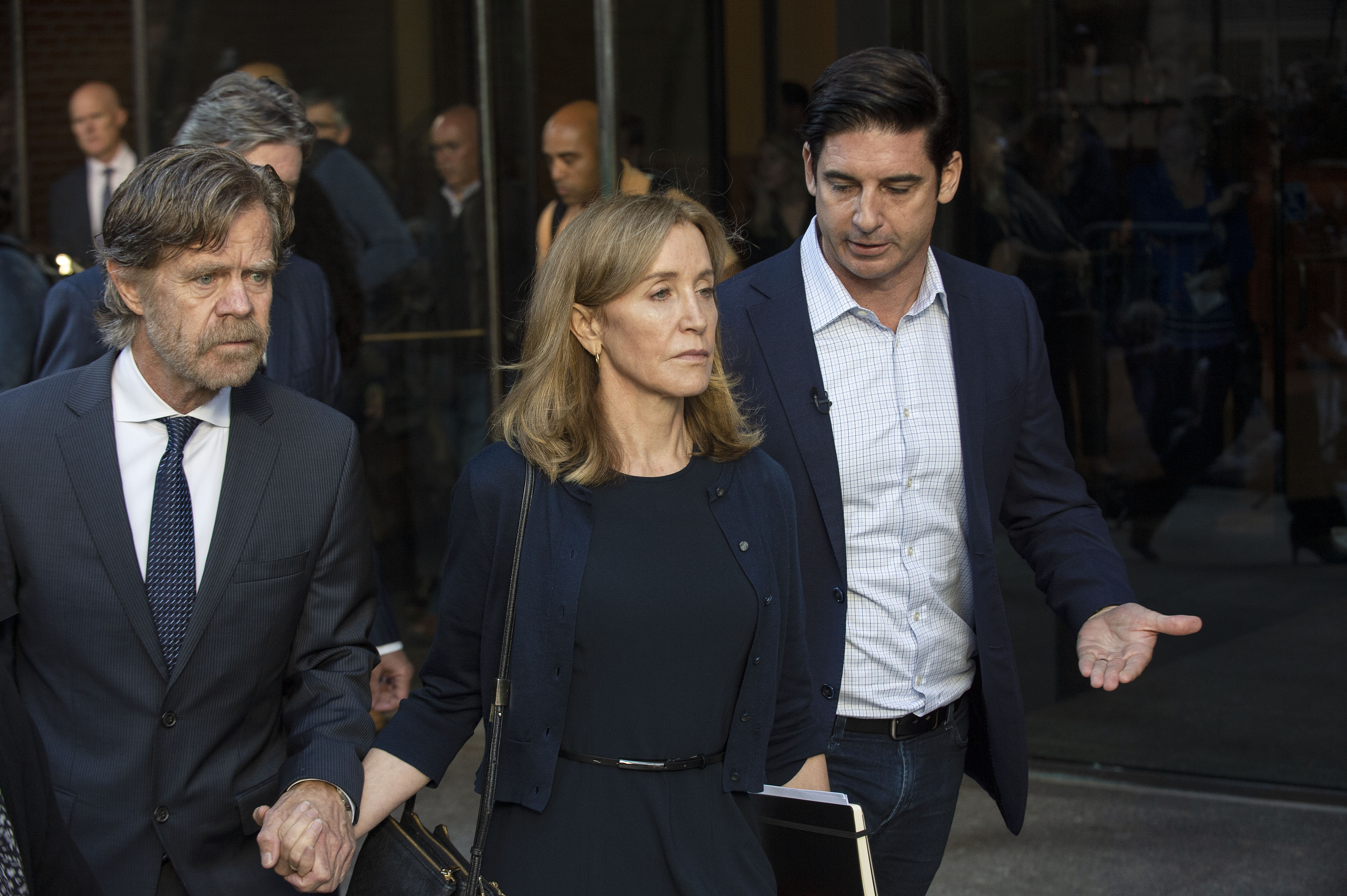 Actress Felicity Huffman, escorted by her husband William H. Macy, exits court in Boston on Sept. 13, 2019.