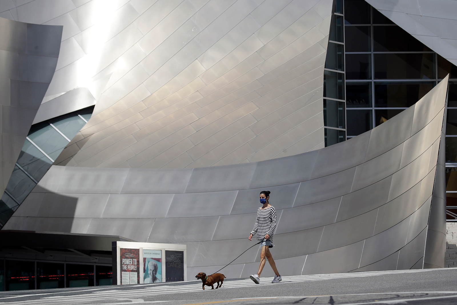 A woman wears a mask while walking with her dog past the Walt Disney Concert Hall on May 14, in Los Angeles.