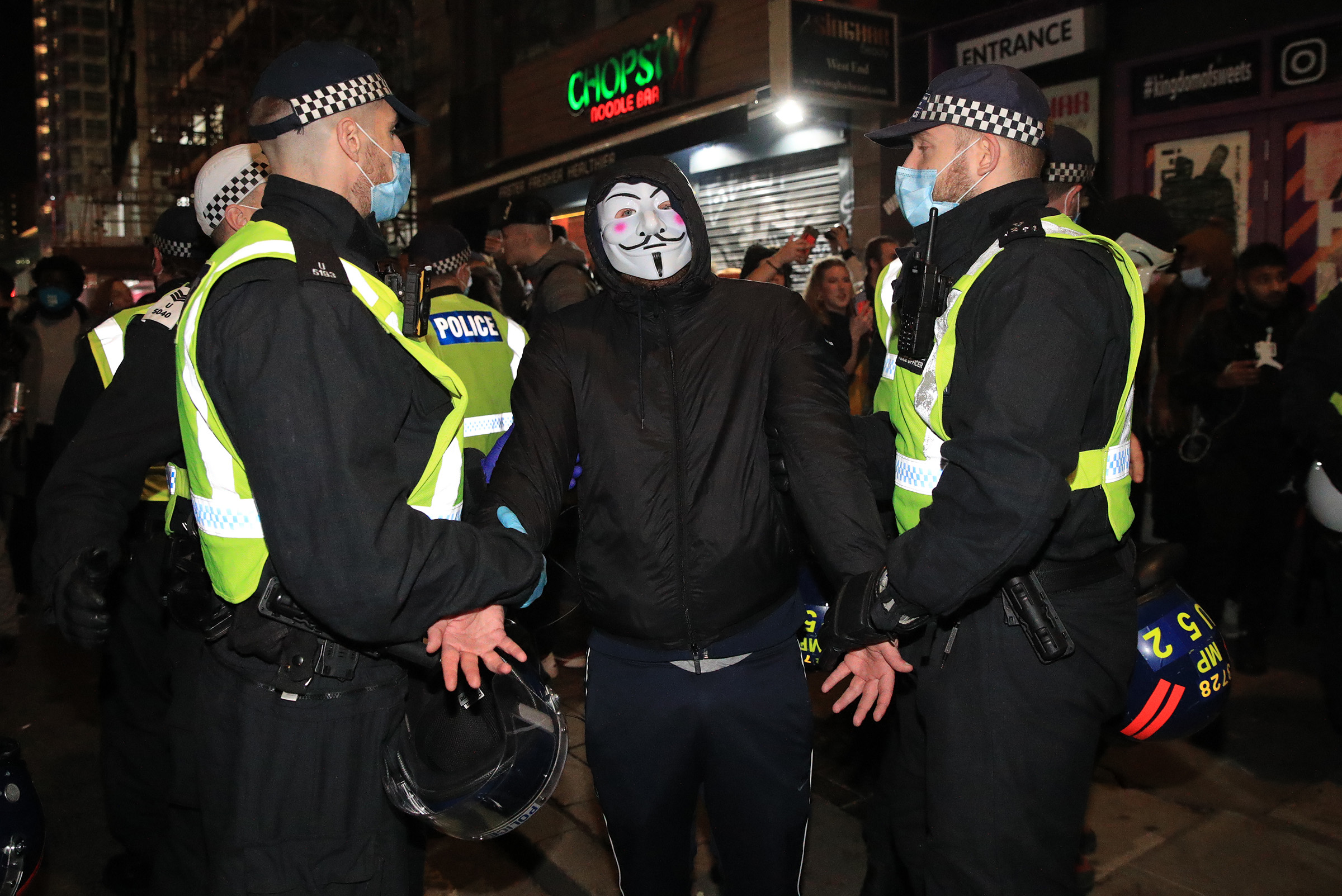Police detain a protester during the Million Mask March anti-establishment protest at Trafalgar Square in London on Thursday, November 5.