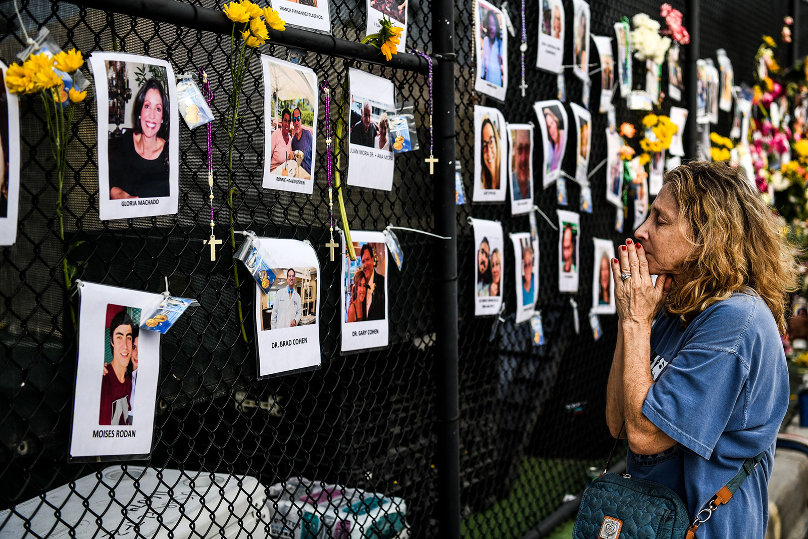 A woman prays in front of photos at the makeshift memorial for the victims of the building collapse, near the site of the accident in Surfside, Florida, north of Miami Beach on June 27.