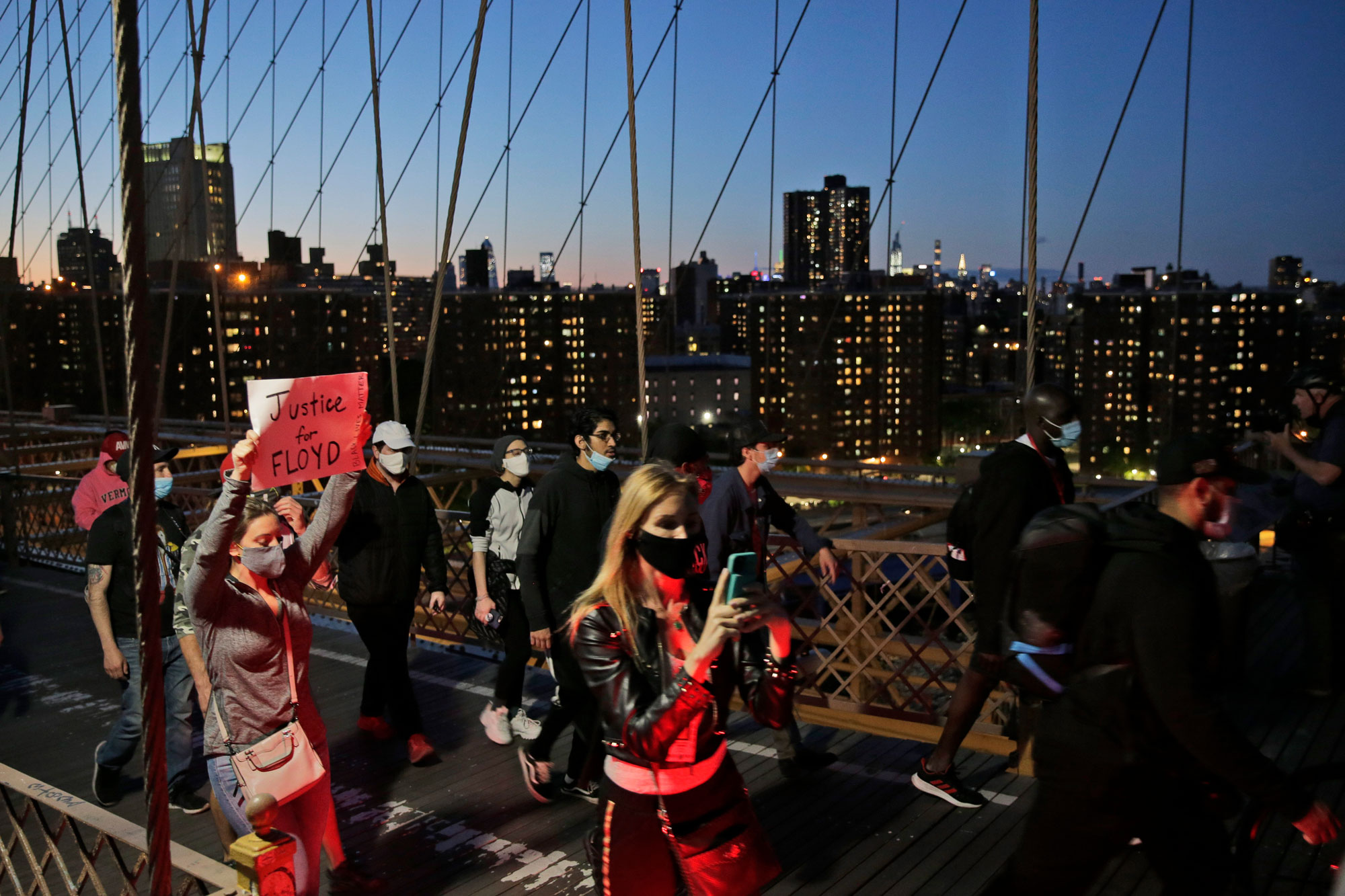 Protesters walk across the Brooklyn Bridge in New York on Sunday, May 31.