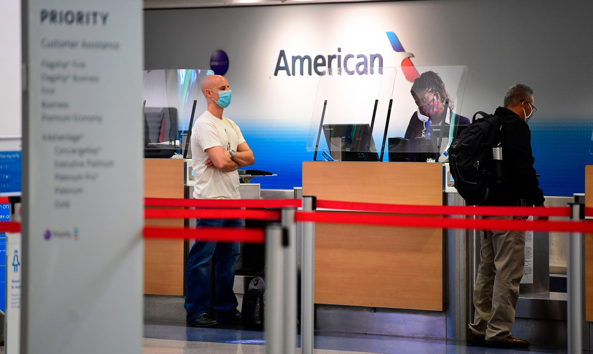 Travelers are seen at the American Airlines check-in counter at Los Angeles International Airport in Los Angeles on October 1, 2020.