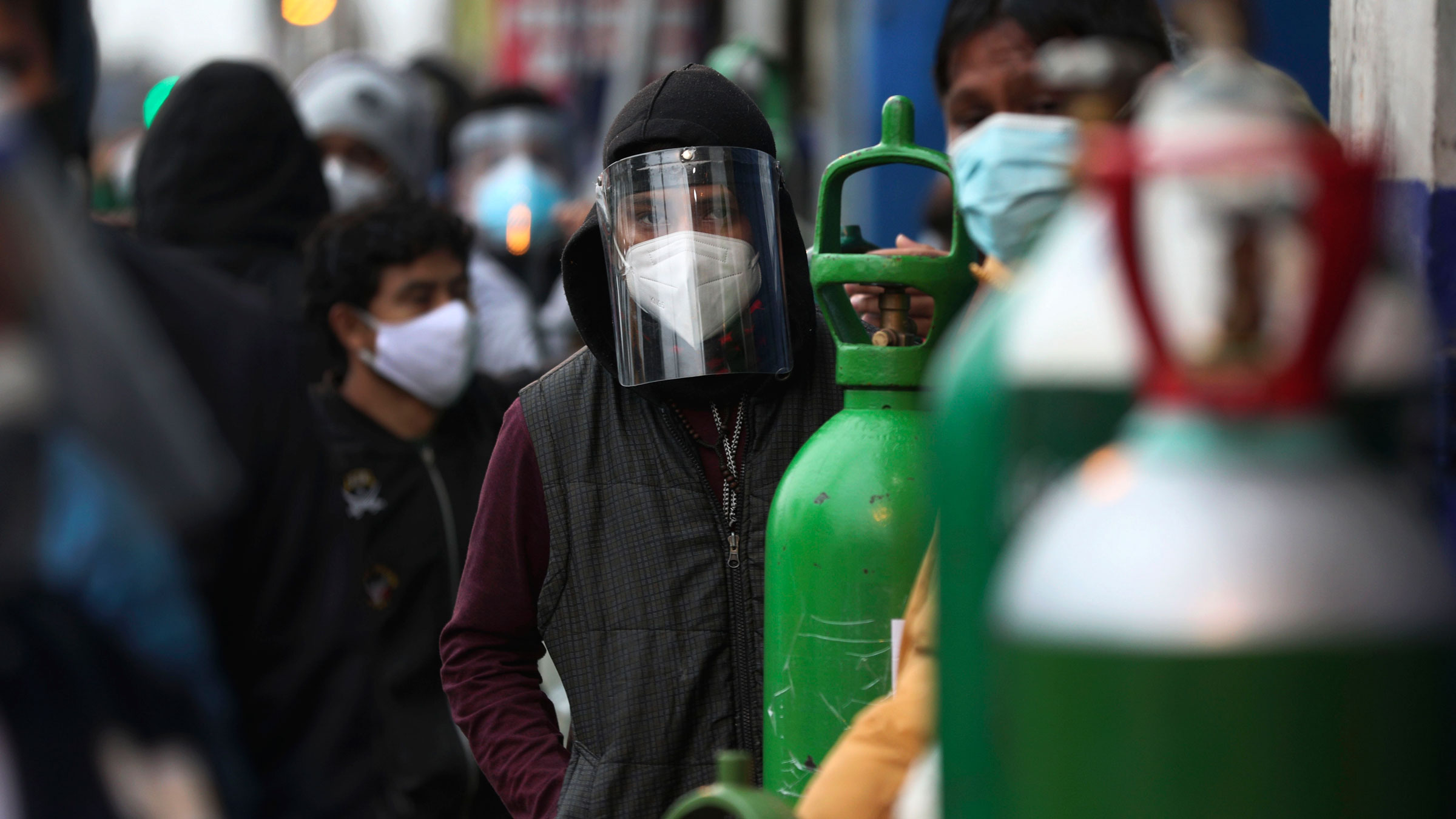 People in Lima, Peru, wait in line to refill oxygen tanks on August 3.