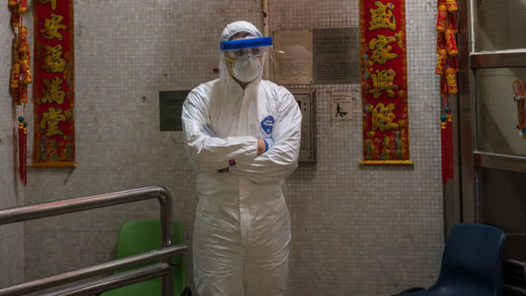 An official stands guard outside an entrance to the Hong Mei House residential building at Cheung Hong Estate in the Tsing Yi district, on Tuesday, February 11, in Hong Kong.