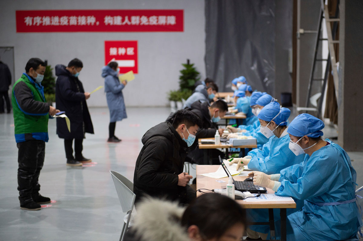 Residents fill out consent forms before receiving their Covid-19 vaccinations at a temporary vaccination site in Beijing, China on January 2.