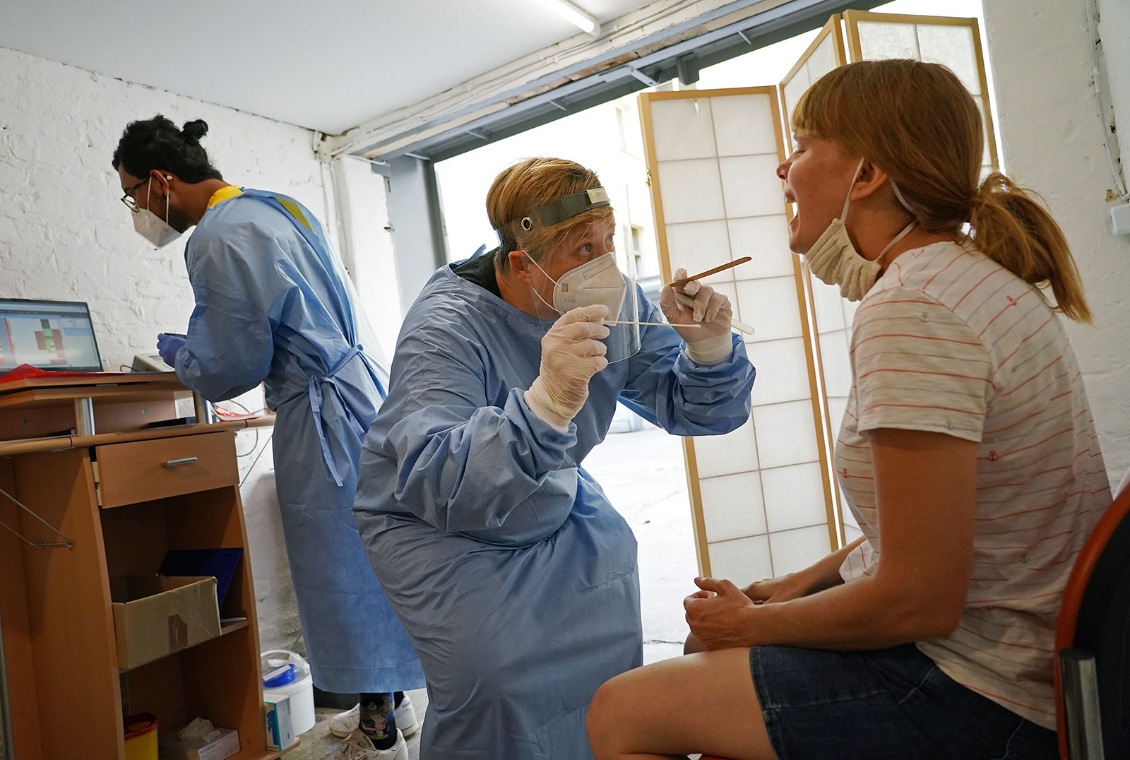 Dr. Wiebke Bergner takes a throat swab sample from a woman seeking a test for possible Covid-19 infection during the novel coronavirus pandemic on August 7, in Berlin, Germany.