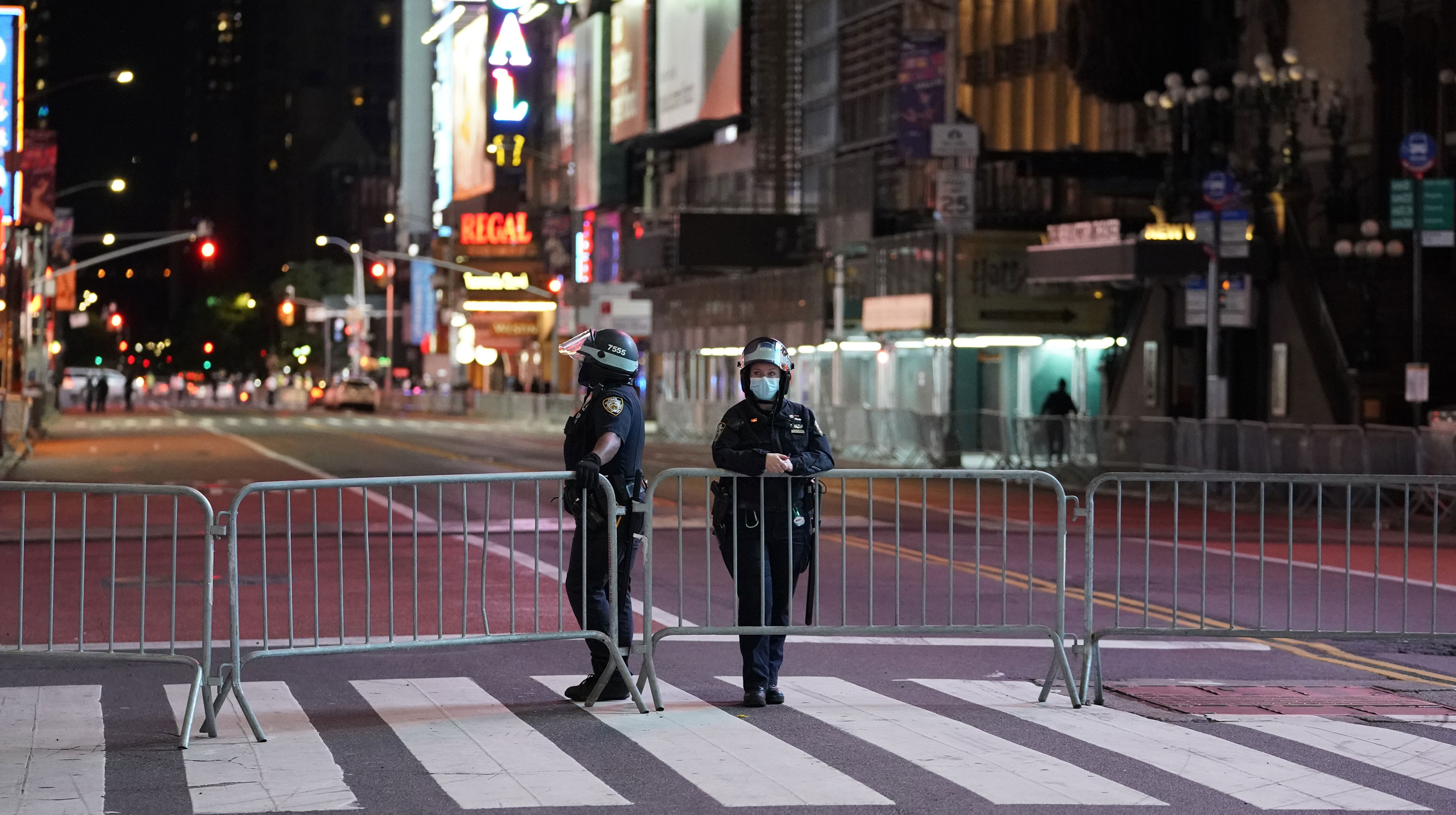 Police officers lean against a barricade in a closed off Times Square shorty before the 11 p.m. curfew went into effect June 1 in New York City.