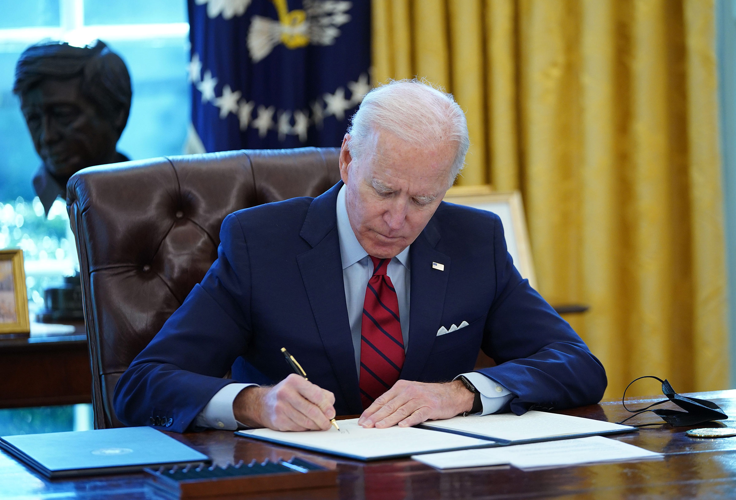 President Joe Biden signs executive orders on health care in the Oval Office of the White House in Washington, DC, on January 28.