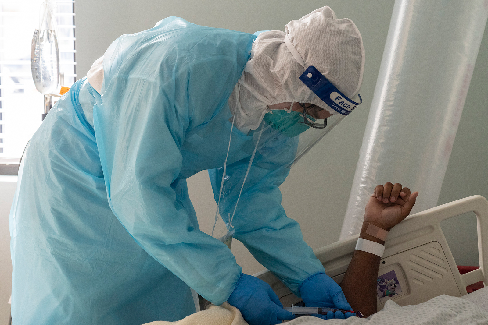 A medical worker takes a blood sample from a Covid-19 patient in the intensive care unit at the United Memorial Medical Center in Houston, on November 22.