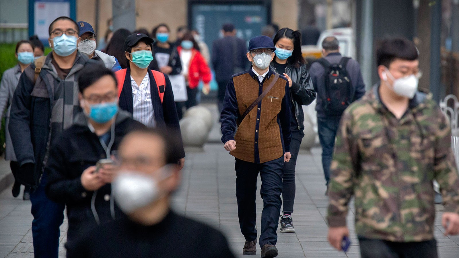 Commuters wear face masks to protect against the spread of new coronavirus as they walk along a street in Beijing on April 9.