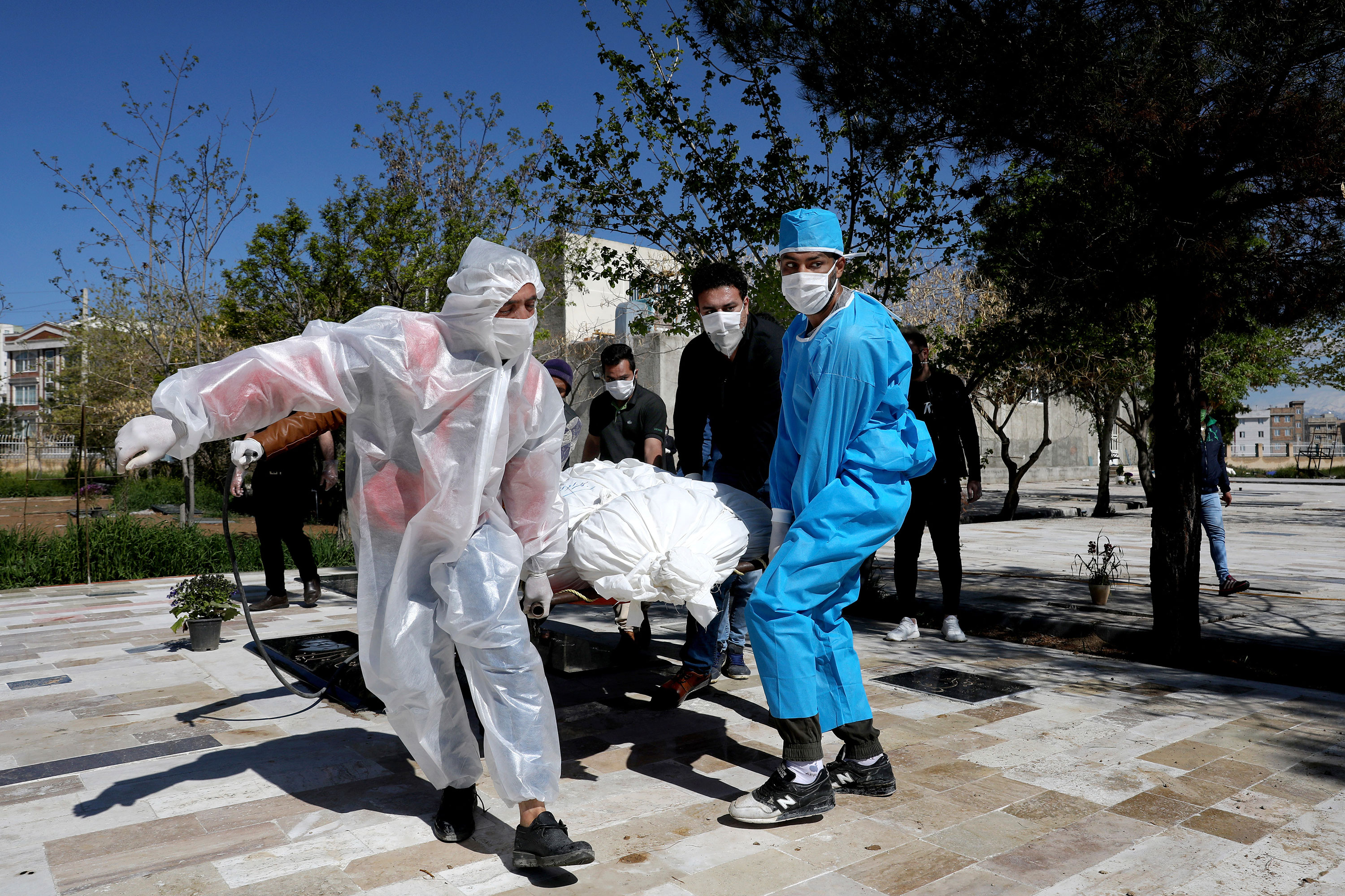 People wear protective clothing while carrying the body of a victim who died from coronavirus at a cemetery just outside Tehran, Iran, on March 30.