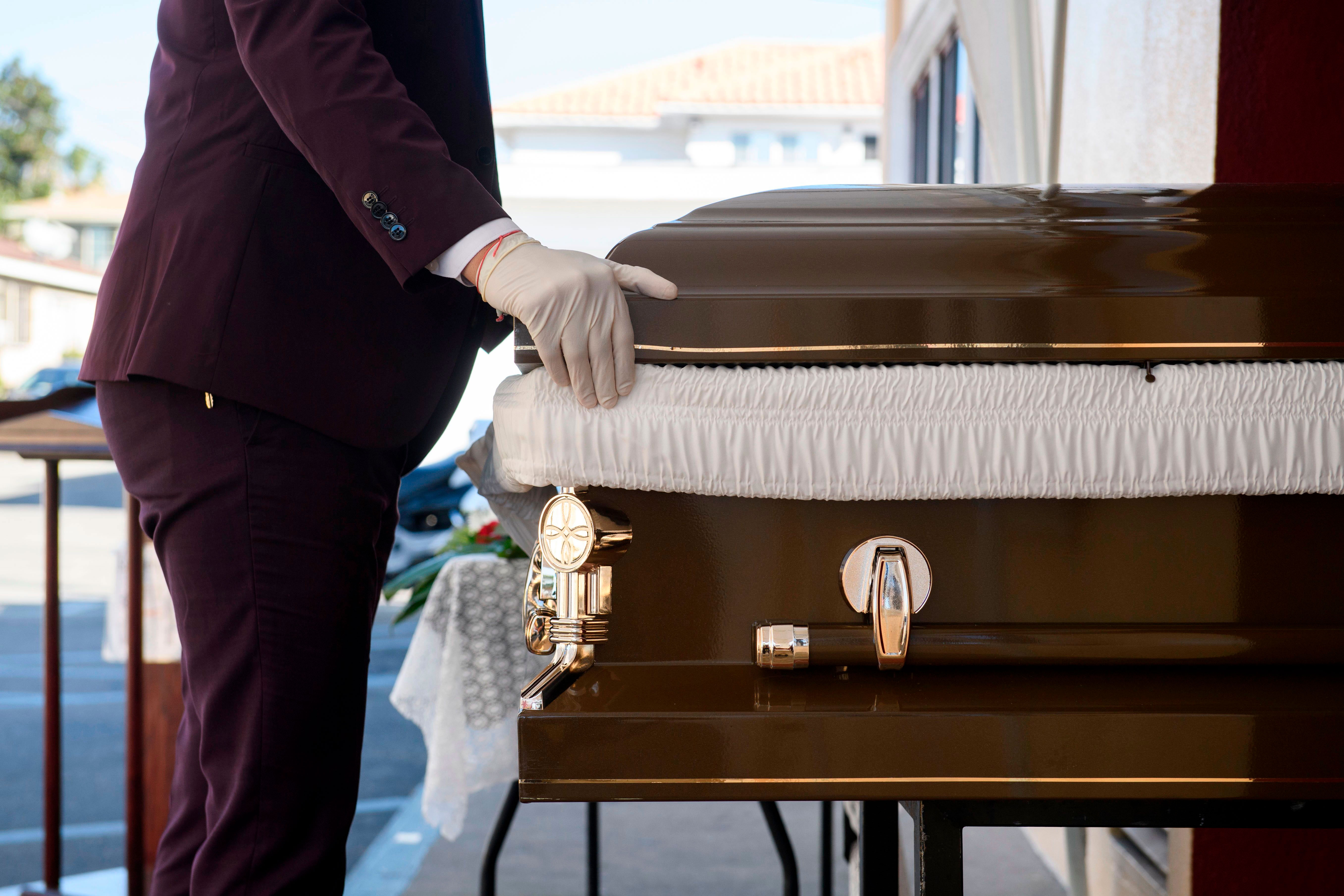 Funeral director Steven Correa moves the casket of someone said to have died from Covid-19 in preparation for burial at Continental Funeral Home in East Los Angeles, California, on December 31, 2020.