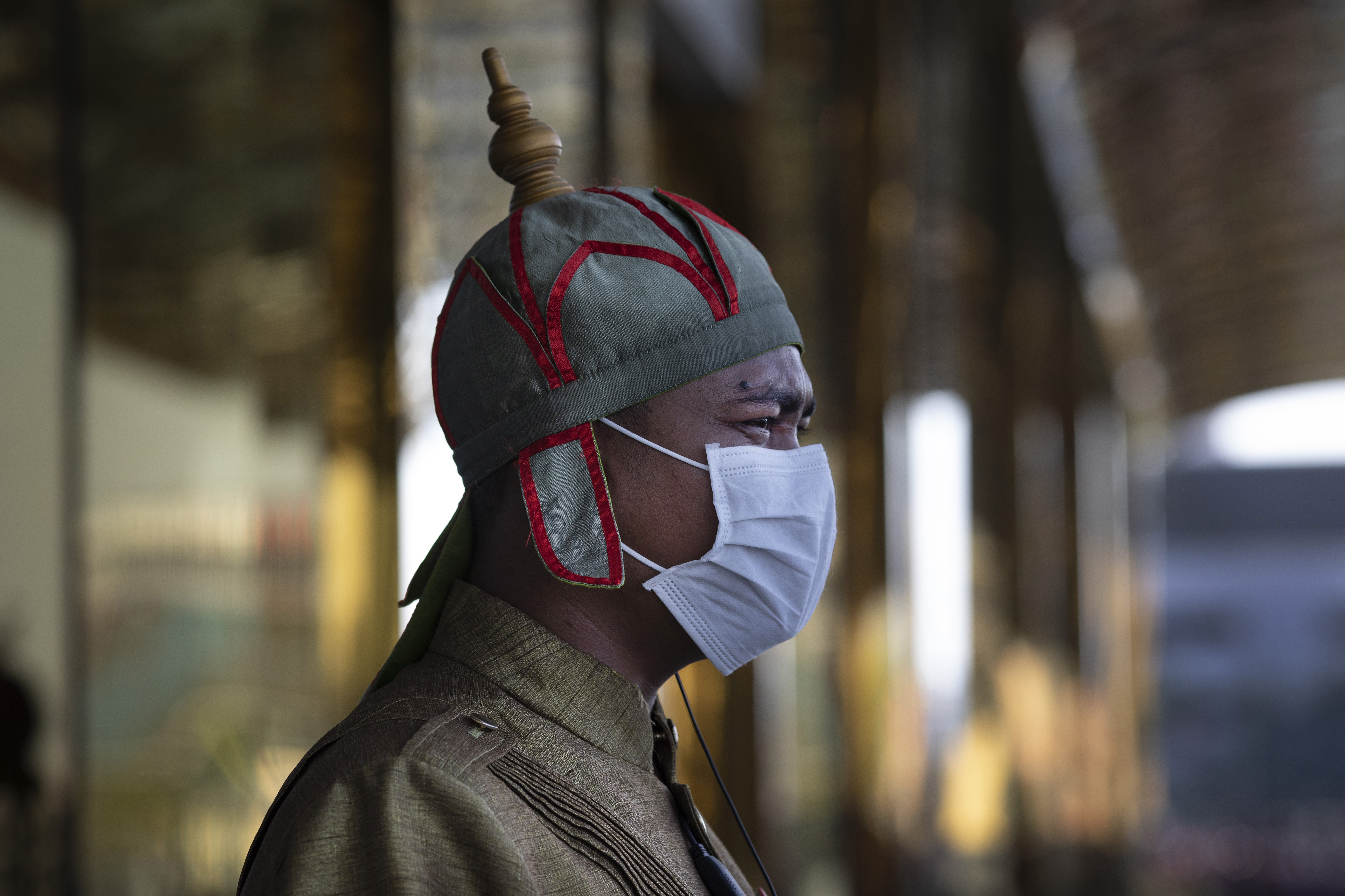 A Cambodian hotel guard wearing a mask stands outside a hotel in Phnom Penh, Cambodia.