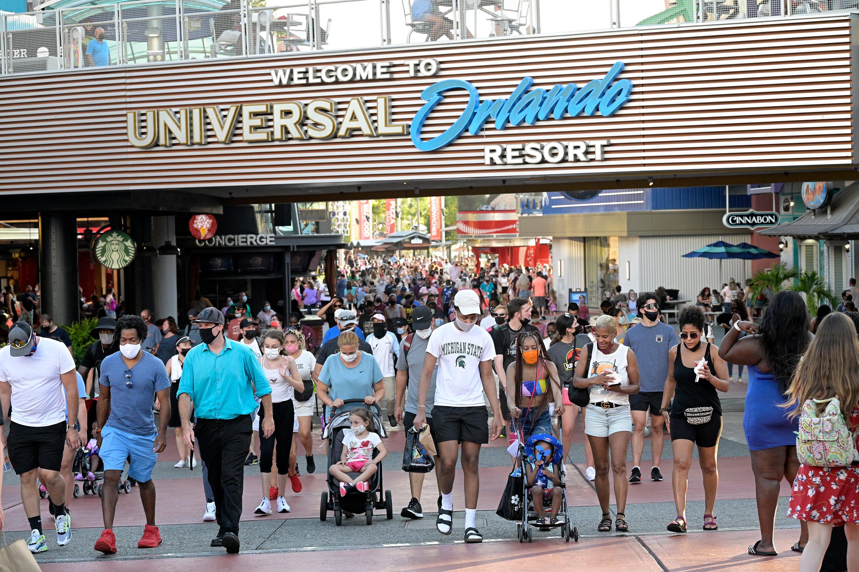 People wear face masks while walking through Universal CityWalk on May 5, in Orlando, Florida.