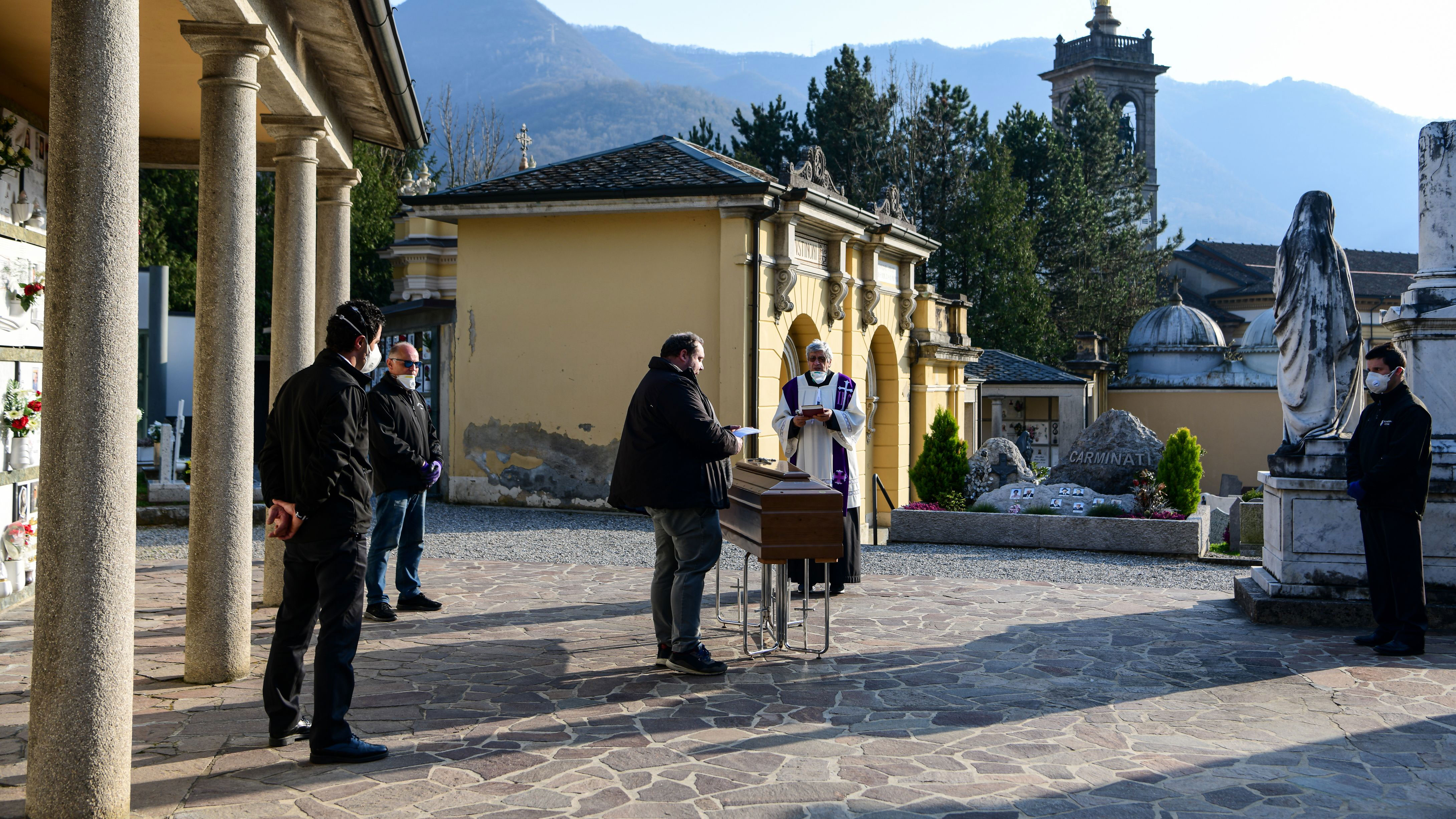 A priest conducts a funeral service without relatives inside the cemetery of Zogno, Italy, on March 21.