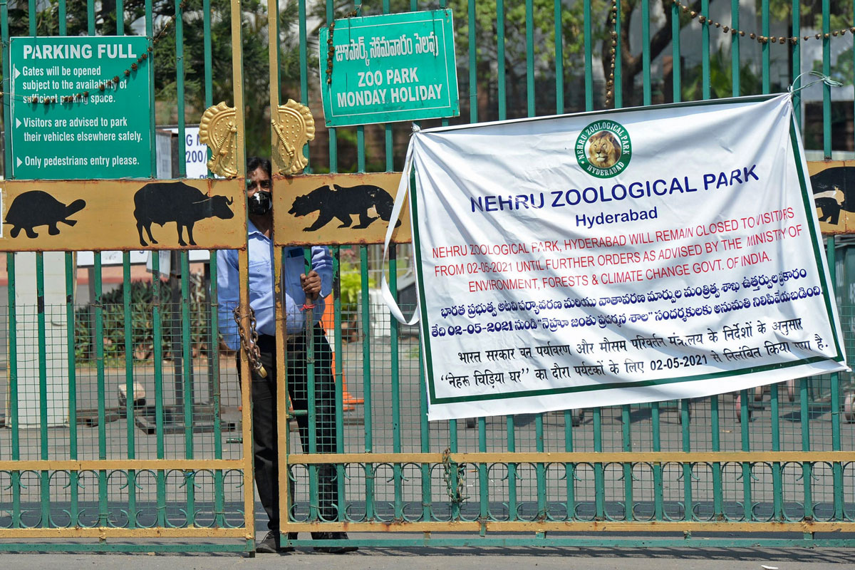 A security guard watches through the entrance gate of the Nehru Zoological Park after it was closed for visitors amid the coronavirus pandemic in Hyderabad, India on May 4.