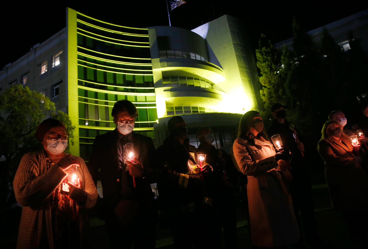 Dr. Chris Farnitano, second from left, and others light candles during an event remembering the 734 Contra Costa County residents who died from Covid-19. The event was held at the Contra Costa Regional Medical Center in Martinez, California on March 22.