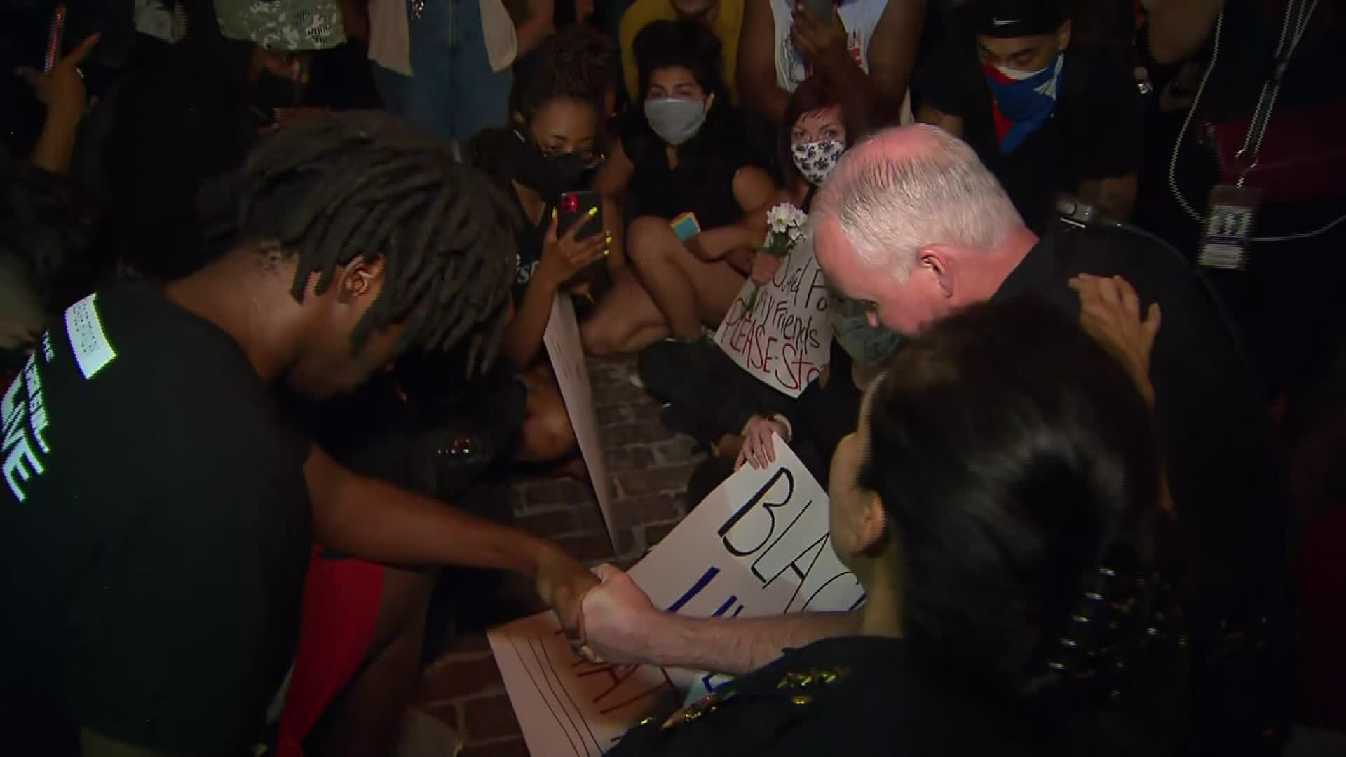 Fort Worth Police Chief Ed Kraus takes a knee with protesters in Fort Worth, Texas, on June 2.