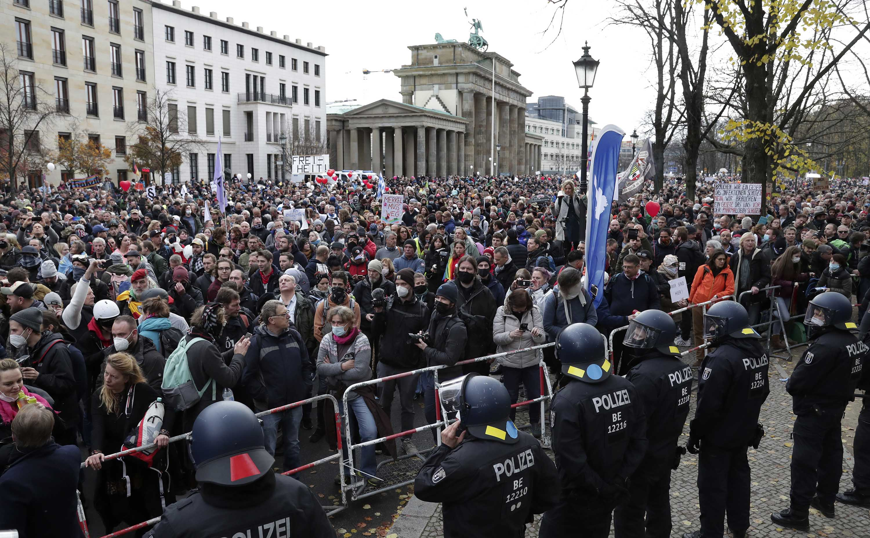Police officers block a road as people attend a protest rally in front of the Brandenburg Gate in Berlin, Germany, on Wednesday.