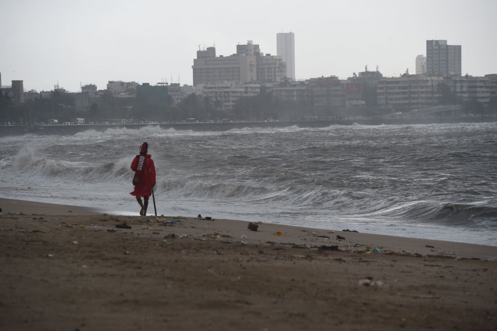 A lifeguard walks along at Girgaum Chowpatty beach following its closure in Mumbai on June 12, 2019.