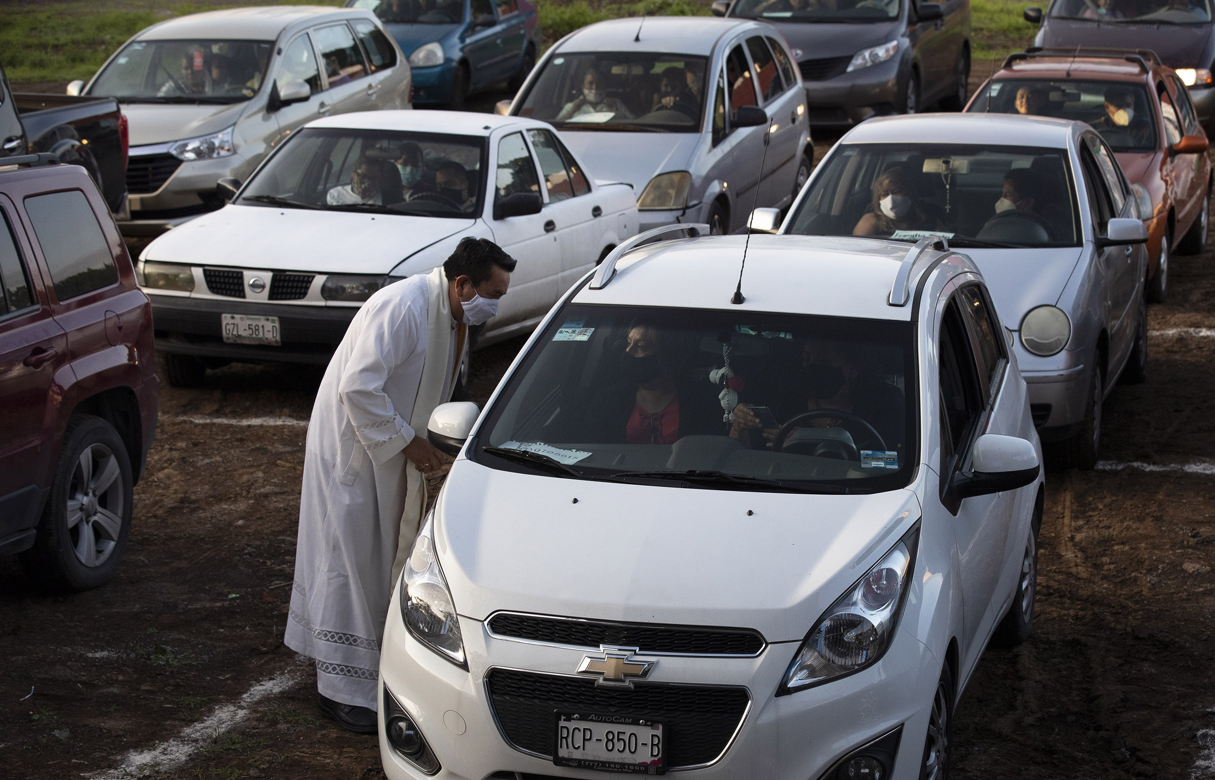 Father Tomas Torres Najera, Vicar of the Cuernavaca Diocese greets parishioners sitting in their cars before Mass at a drive-in cinema in Cuernavaca, Mexico, on Sunday, August 2.