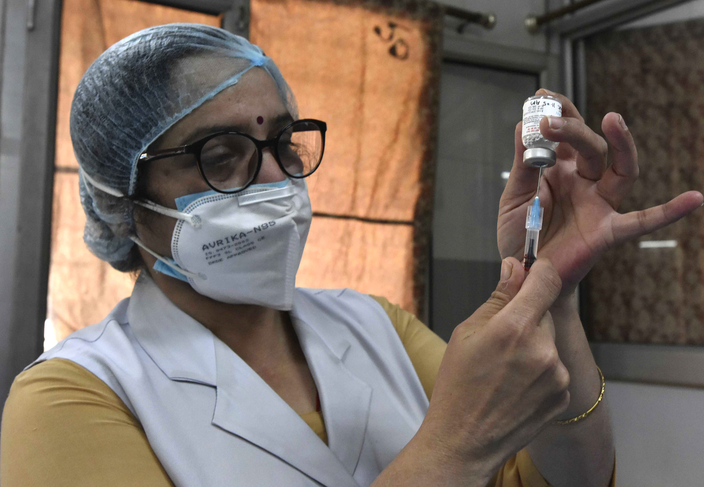 A medic prepares a dose of the Covishield vaccine at Hindu Rao Hospital, on March 22, in New Delhi, India.