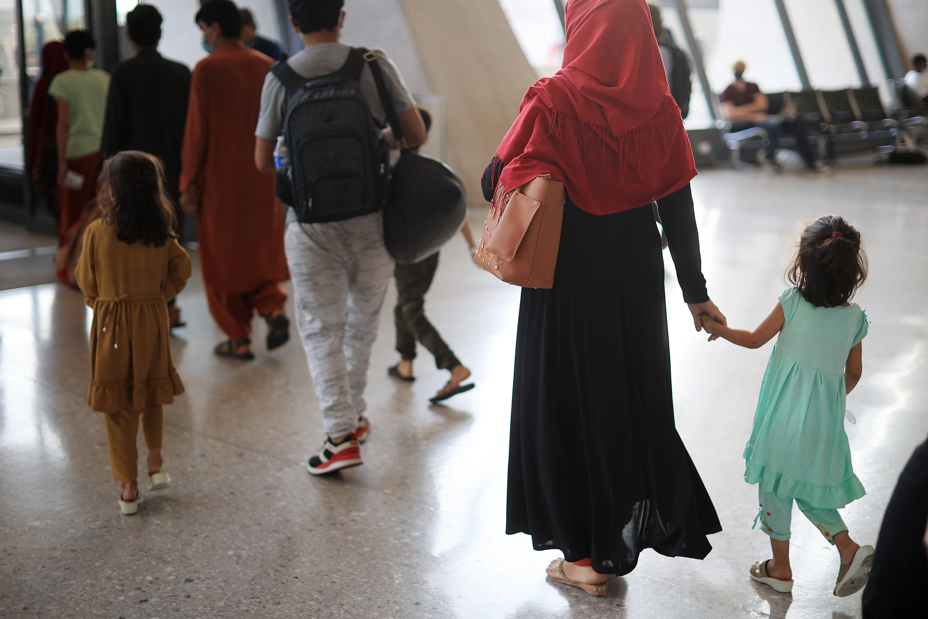 Refugees arrive at Dulles International Airport after being evacuated from Kabul on August 27 in Dulles, Virginia.