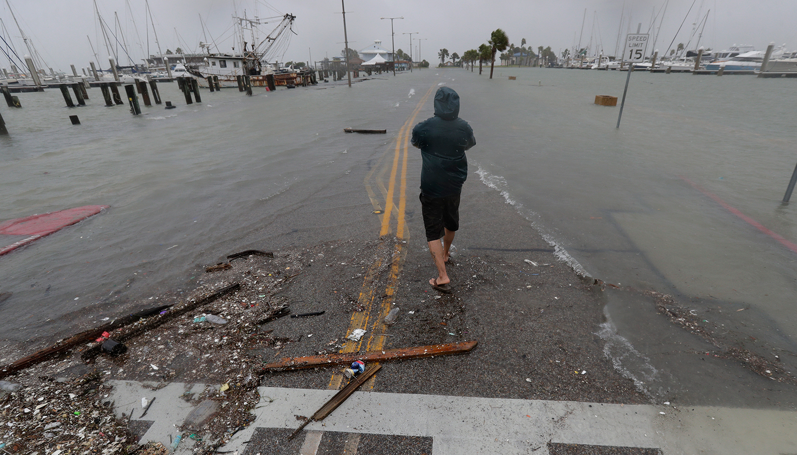 A person walks up a road beginning to flood as Hurricane Hanna makes landfall on Saturday in Corpus Christi, Texas.