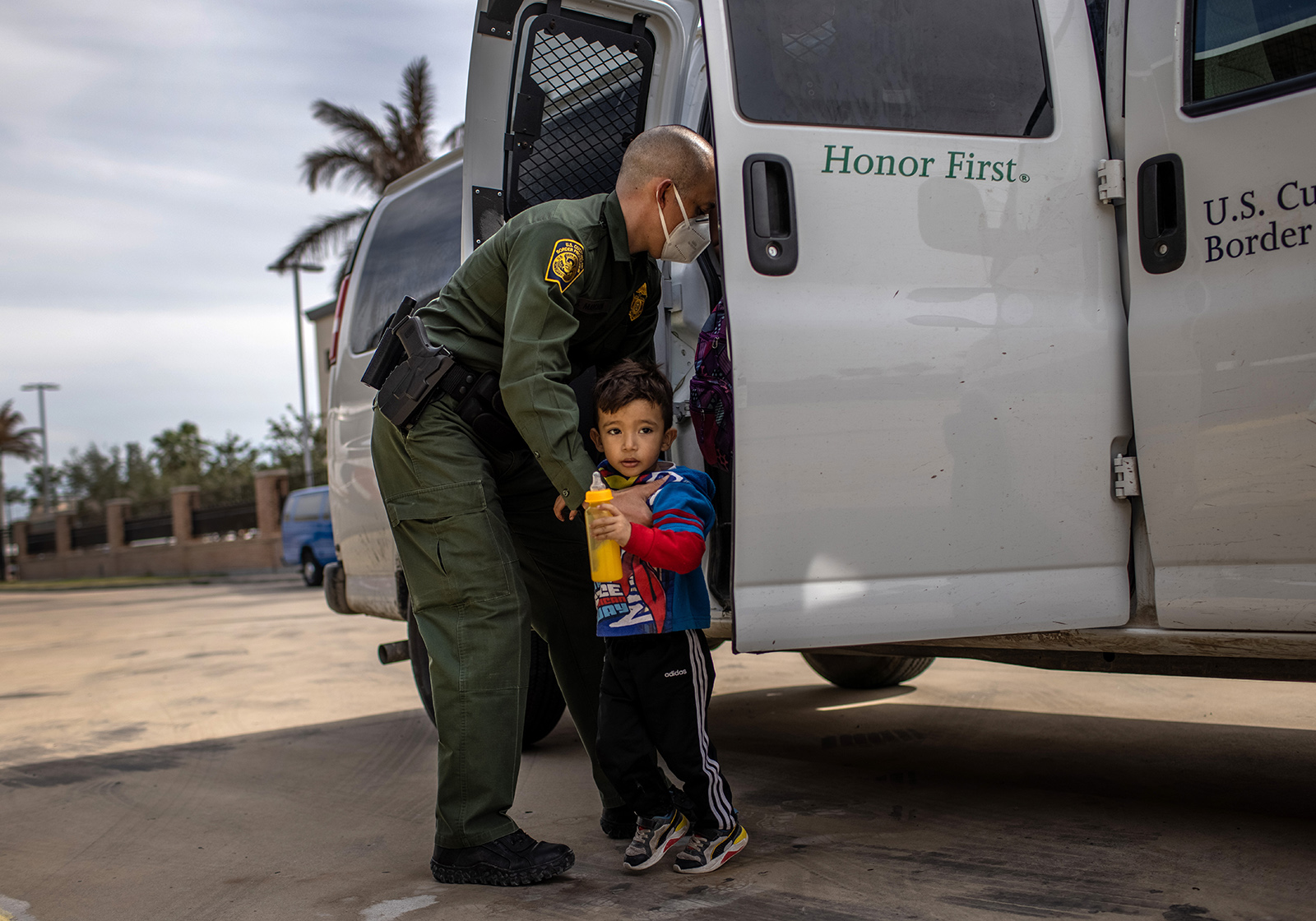A U.S. Border Patrol agent delivers a young asylum seeker and his family to a bus station on February 26, in Brownsville, Texas.