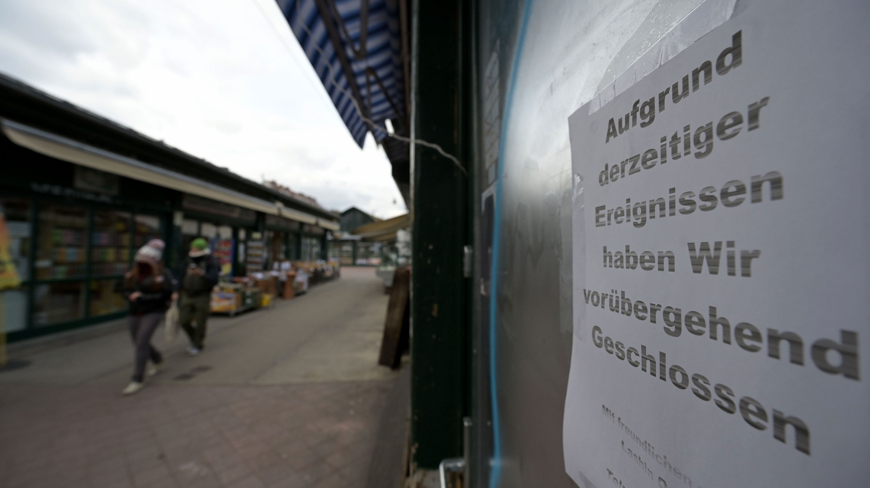 People walk past a closed shop at the Naschmarkt market in Vienna, Austria, on March 30.