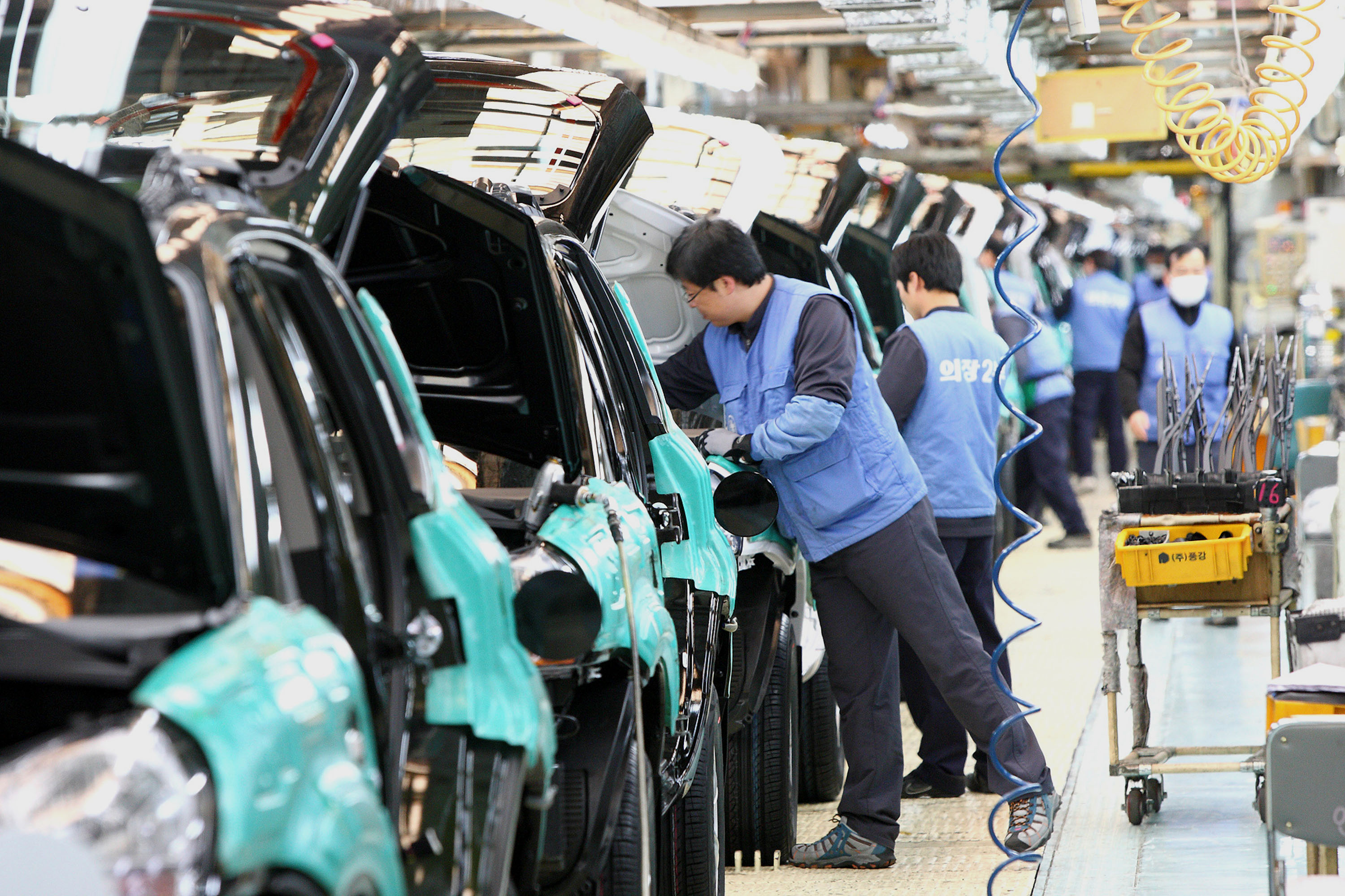 In this 2009 photo, workers work on an assembly line at Hyundai Motor Co. plant in Ulsan, south of Seoul, South Korea. The Hyundai Motor Company is suspending production lines at its plants in South Korea, after its supply of parts was disrupted because of the coronavirus outbreak in China.