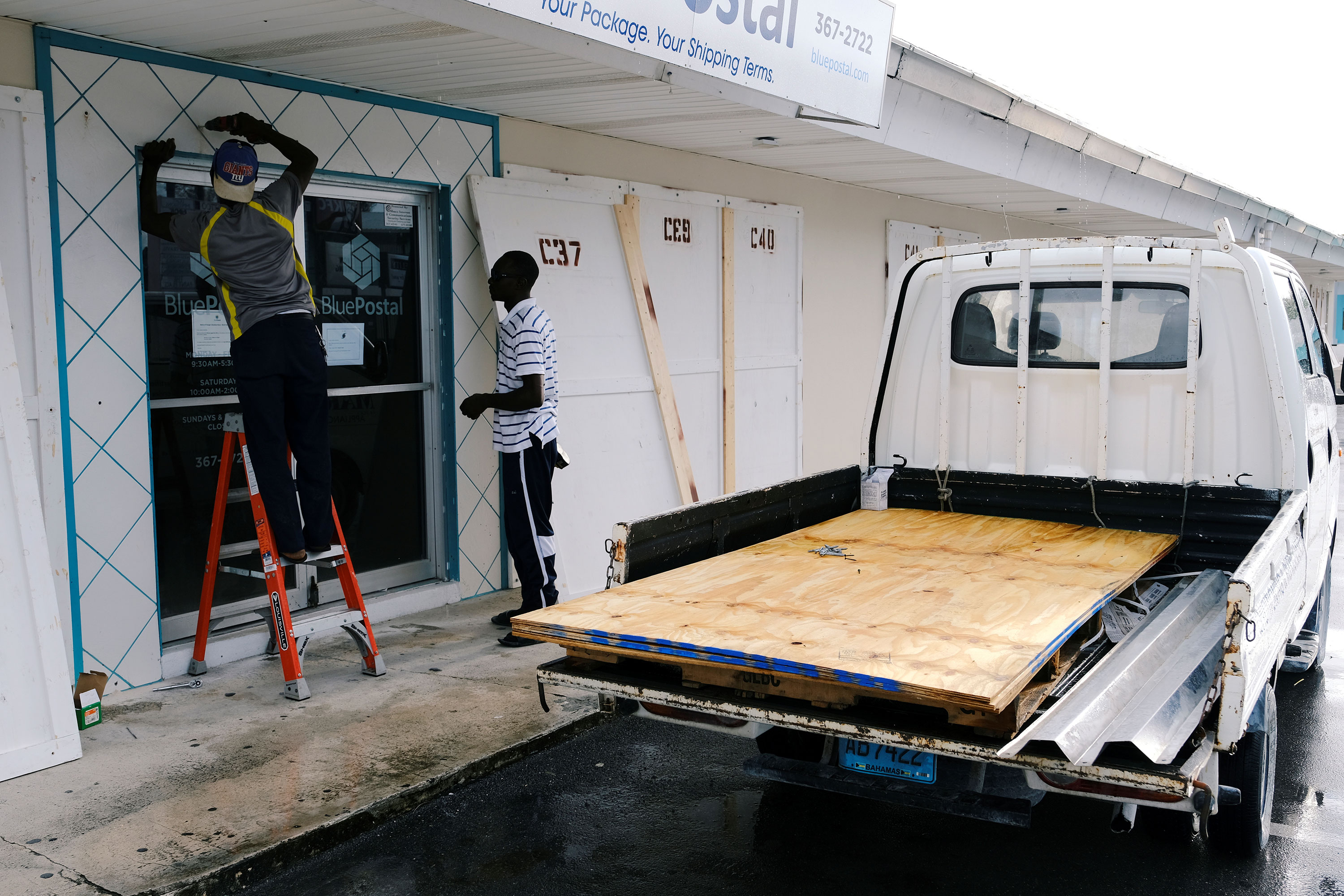 Workers install storm shutters Saturday ahead of Hurricane Dorian's arrival in Marsh Harbour on the Great Abaco Island in the Bahamas.