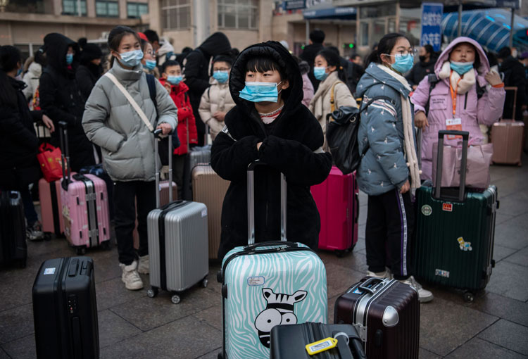 Chinese children wear protective masks as they wait to board trains at Beijing Railway station before the annual Spring Festival.