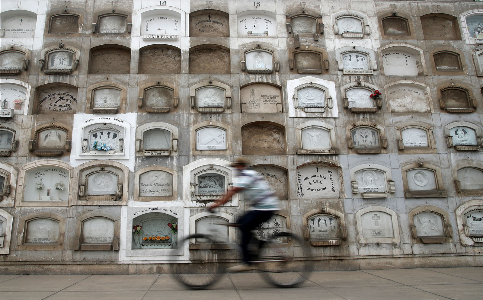 A cemetery worker rides a bicycle to put flowers on the graves at El Angel cemetery on June 4, 2020 in Lima, Peru. Peru has the second-highest number of cases of Covid-19 in Latin America, after Brazil.